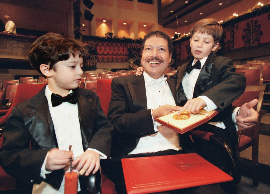 Ahmed Zewail sitting with two children around him in empty theater (© AP Images)