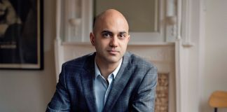 Ayad Akhtar sitting with hands folded on table (© Nina Subin)