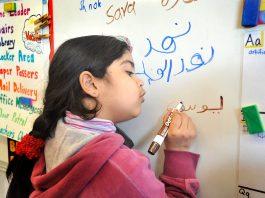 Siswa-siswa AS, seperti gadis muda yang sedang menulis nama adiknya di papan tulis kelas ini, makin banyak yang belajar bahasa Arab. (© Getty Images/Portland Press Herald)