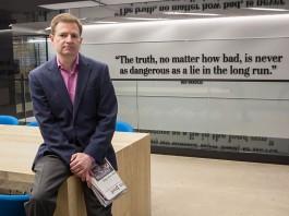 Glenn Kessler sitting on table holding folded newspaper (State Dept./D.A. Peterson)