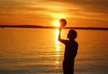 Silhouette of man standing near water in sunset (© Latif Abdul)