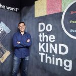 Man standing in front of chalkboards reading 'Do the KIND Thing' (Courtesy of Daniel Lubetzky)