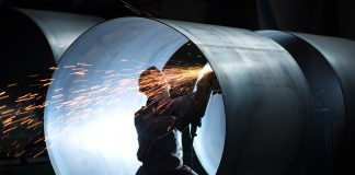 Worker kneeling and welding inside large steel tube (Shutterstock)