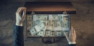 Pair of hands opening briefcase full of money (Shutterstock)