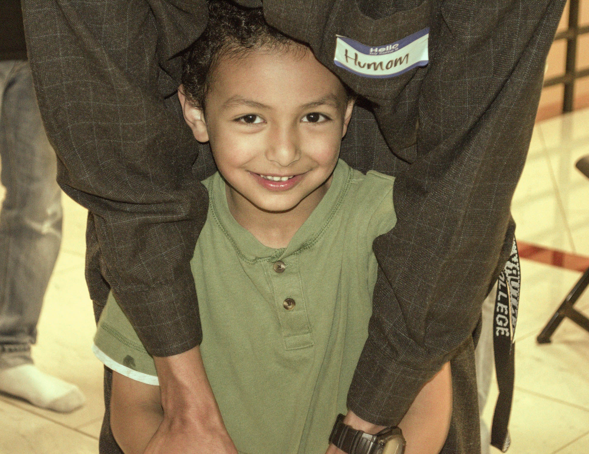 Smiling boy in his father's arms (Courtesy of MAS Minnesota)