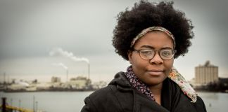 Destiny Watford standing near Baltimore harbor with smoke pluming from industrial buildings in the background (Courtesy of Goldman Environmental Prize)