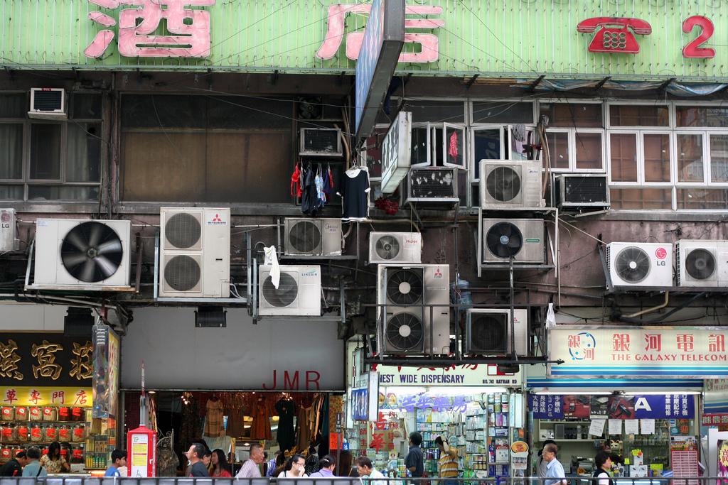 Une douzaine de climatiseurs accrochés à un mur extérieur (Flickr/Niall Kennedy)