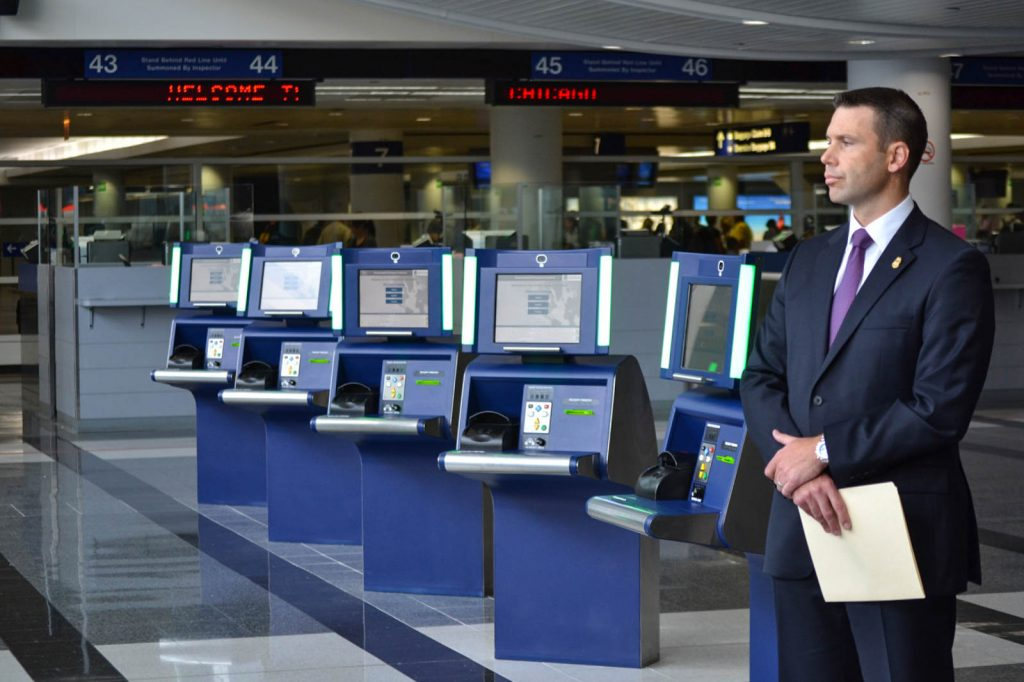 Suited man standing next to passport kiosks at airport (U.S. Customs and Border Protection)