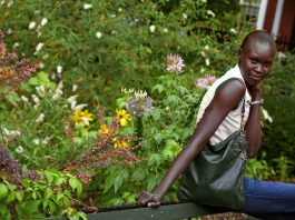 Woman sitting in leafy arbor (© AP Images)