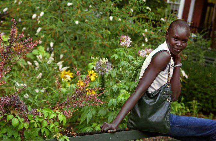Mulher sentada em estrutura rodeada de vegetação (© AP Images)