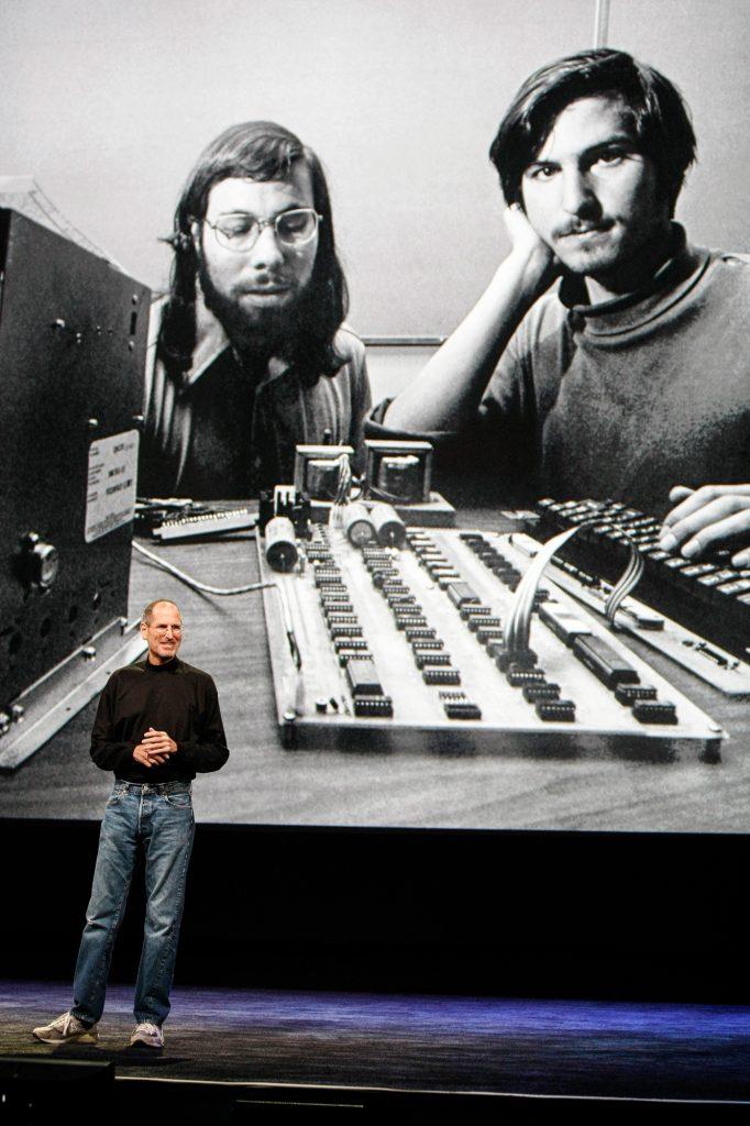 Steve Jobs, debout devant la projection d'une photo en noir et blanc de Steve Wozniak et de lui-même plus jeunes, avec un vieux micro-ordinateur (© AP Images)