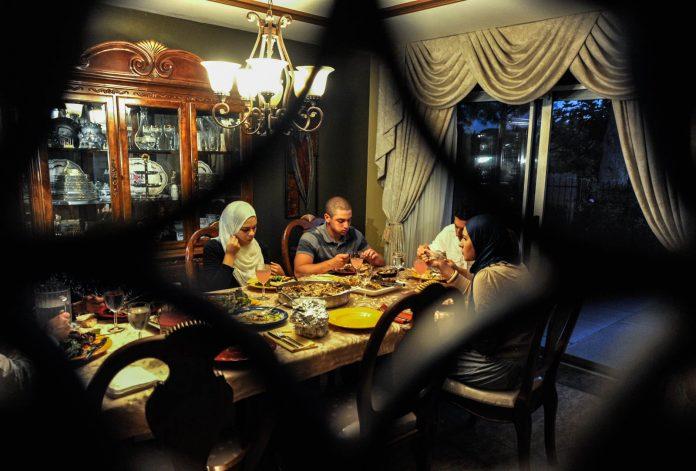 Família à mesa de jantar após o anoitecer (© AP Images)