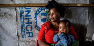 Woman and child sitting in shelter (© AP Images)