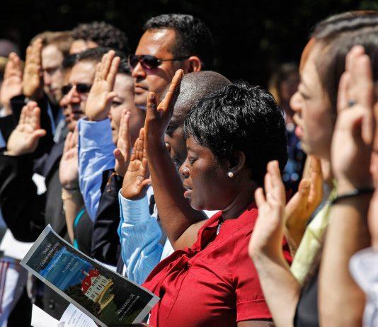 Une rangée de personnes, la main droite levée, en train de prêter serment (©APImages)