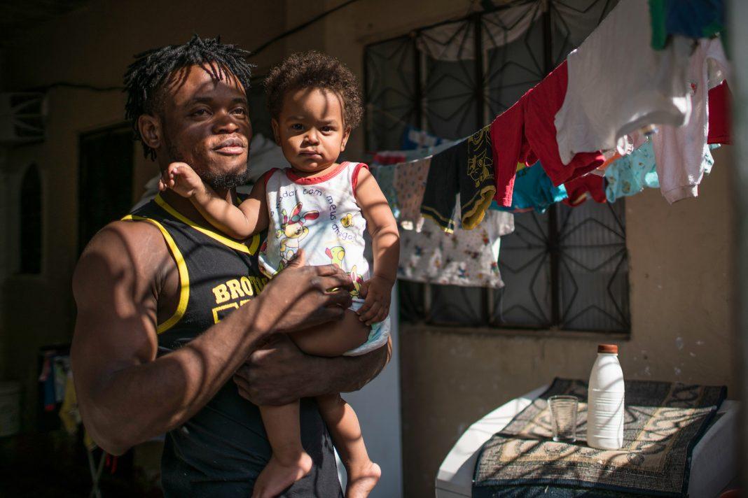 Popole Misenga holding child (© AP Images)