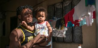 Popole Misenga sostiene a un niño en brazos (© AP Images)