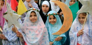 Girls in hijabs holding paper crescents and stars (© AP Images)