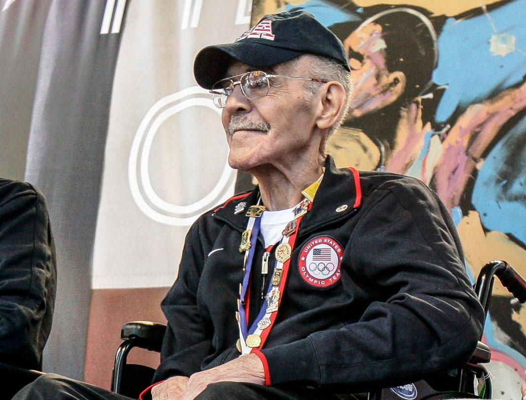 رجل مسنّ جالس أمام لوجة جدارية © AP Images