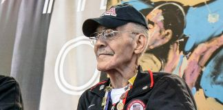 Elderly man sitting in front of mural (© AP Images)