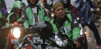 Men sitting on motorcycles along street (© AP Images)