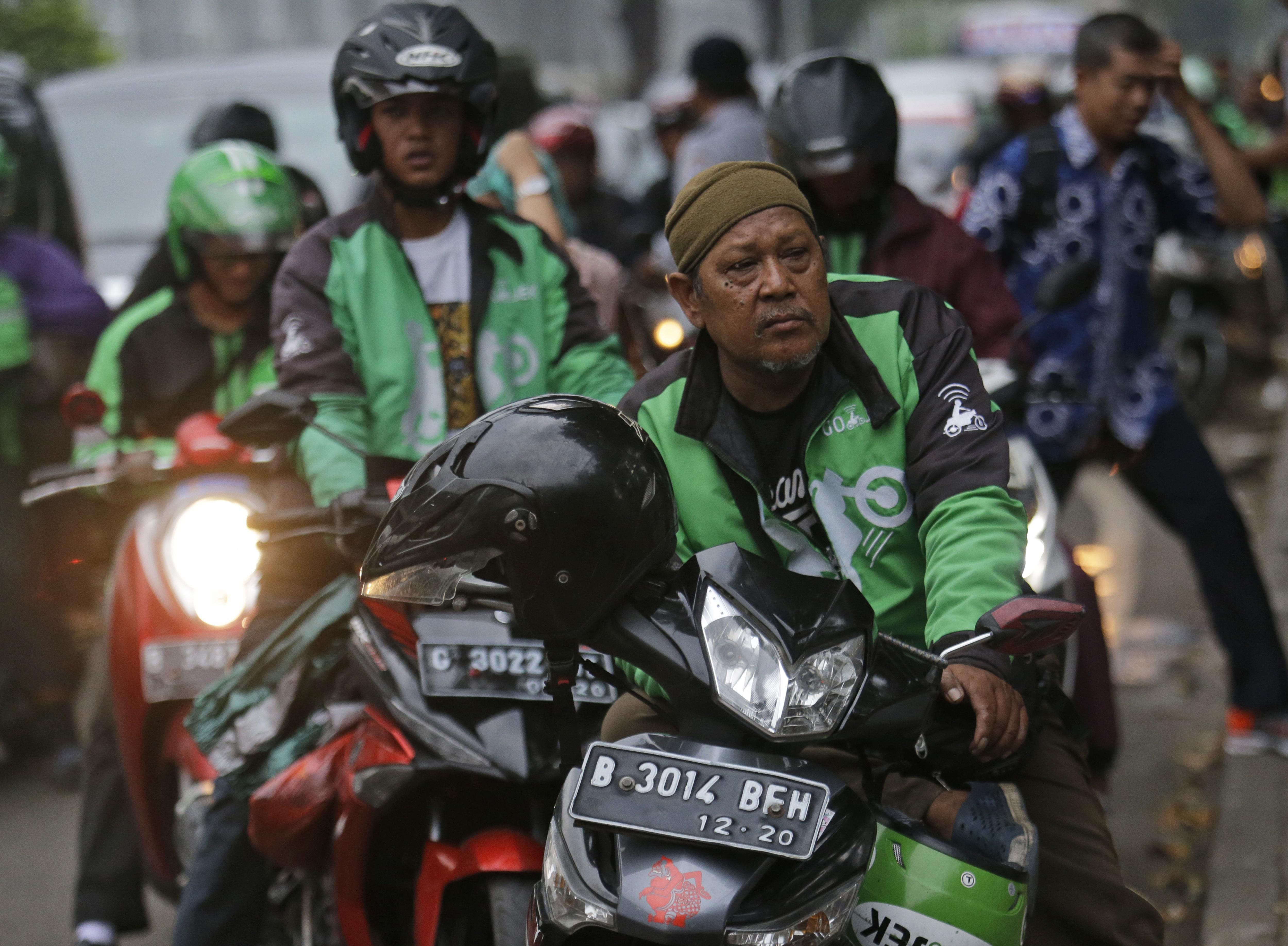 Hombres sentados en motocicletas a lo largo de una calle (© AP Images)