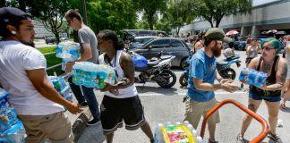 Fila de pessoas descarregando caixas de água (© AP Images)
