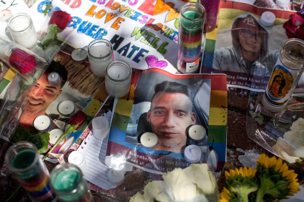 Pilha de fotos, velas, flores e mensagens (© AP Images)