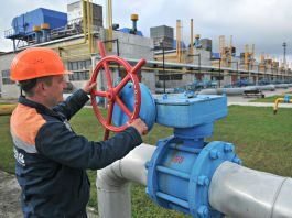 Man wearing hard hat turning valve on pipeline (© AP Images)