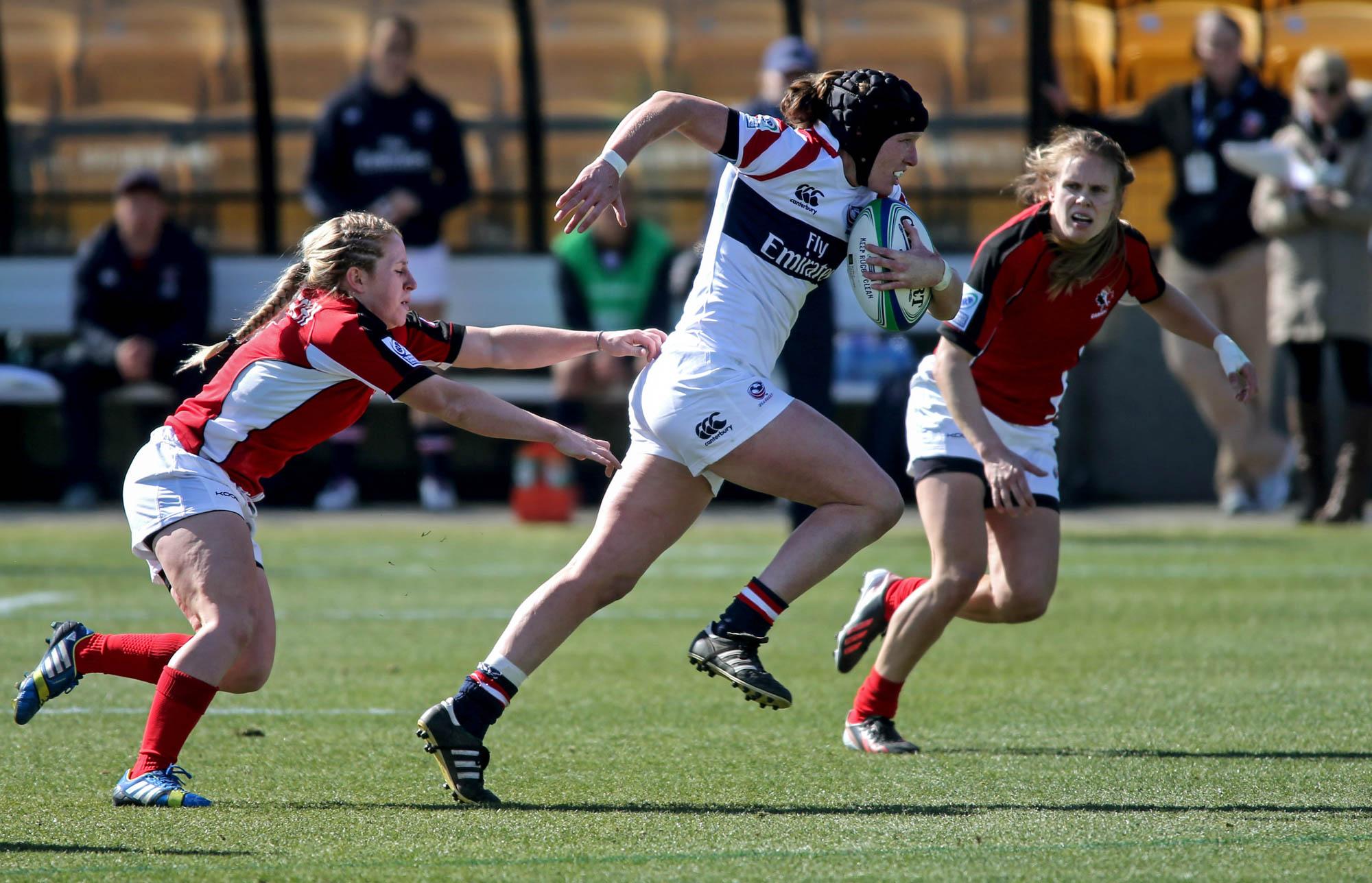 Mujer con pelota de rugby en un brazo escapa de rivales (© AP Images)
