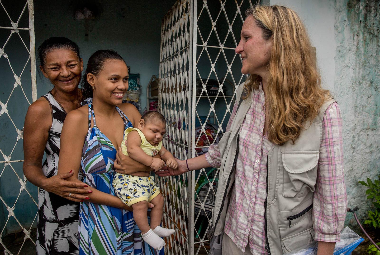 Три женщины беседуют; одна из них держит ребенка (© AP Images)