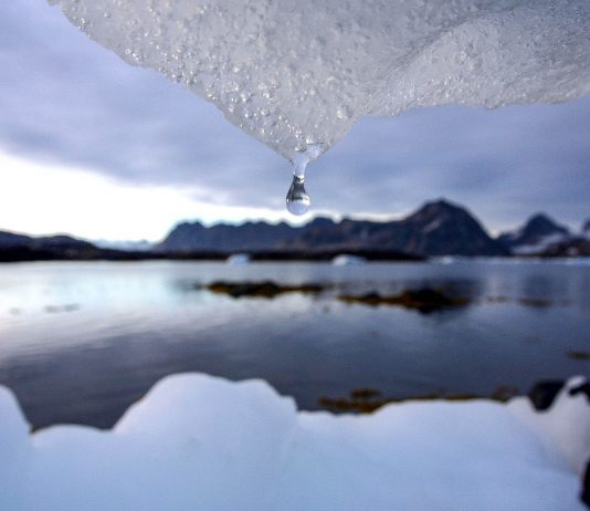 Drop of water hanging from melting iceberg (© AP Images)