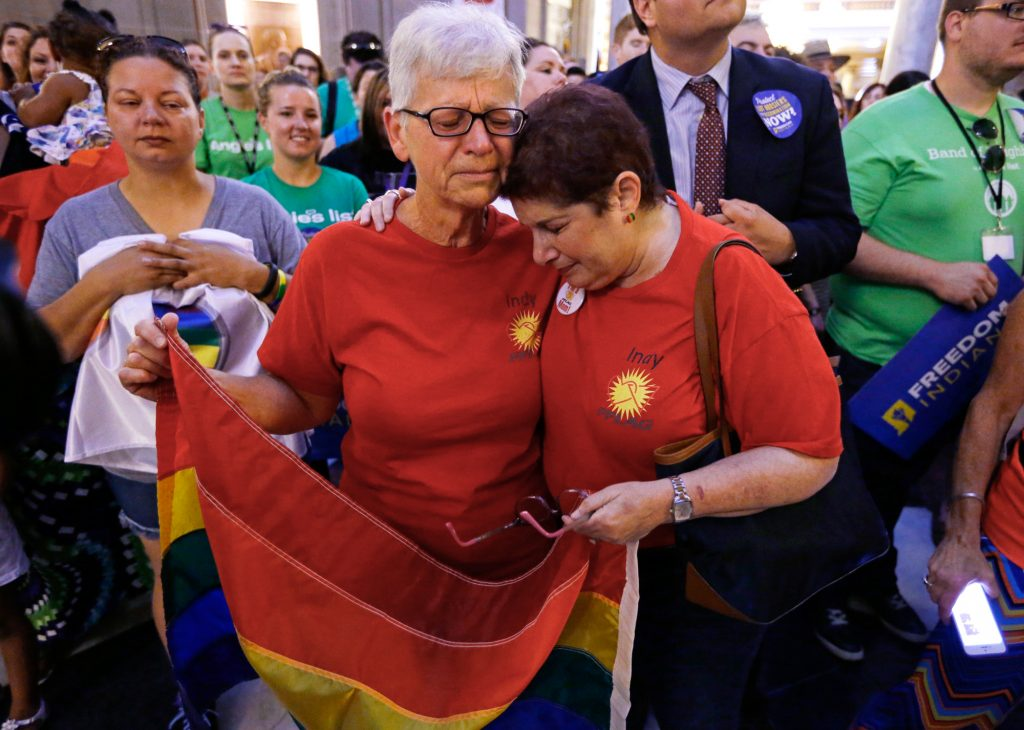 Two women standing in crowd wrapping an arm around each other and holding rainbow flag (©AP Images)