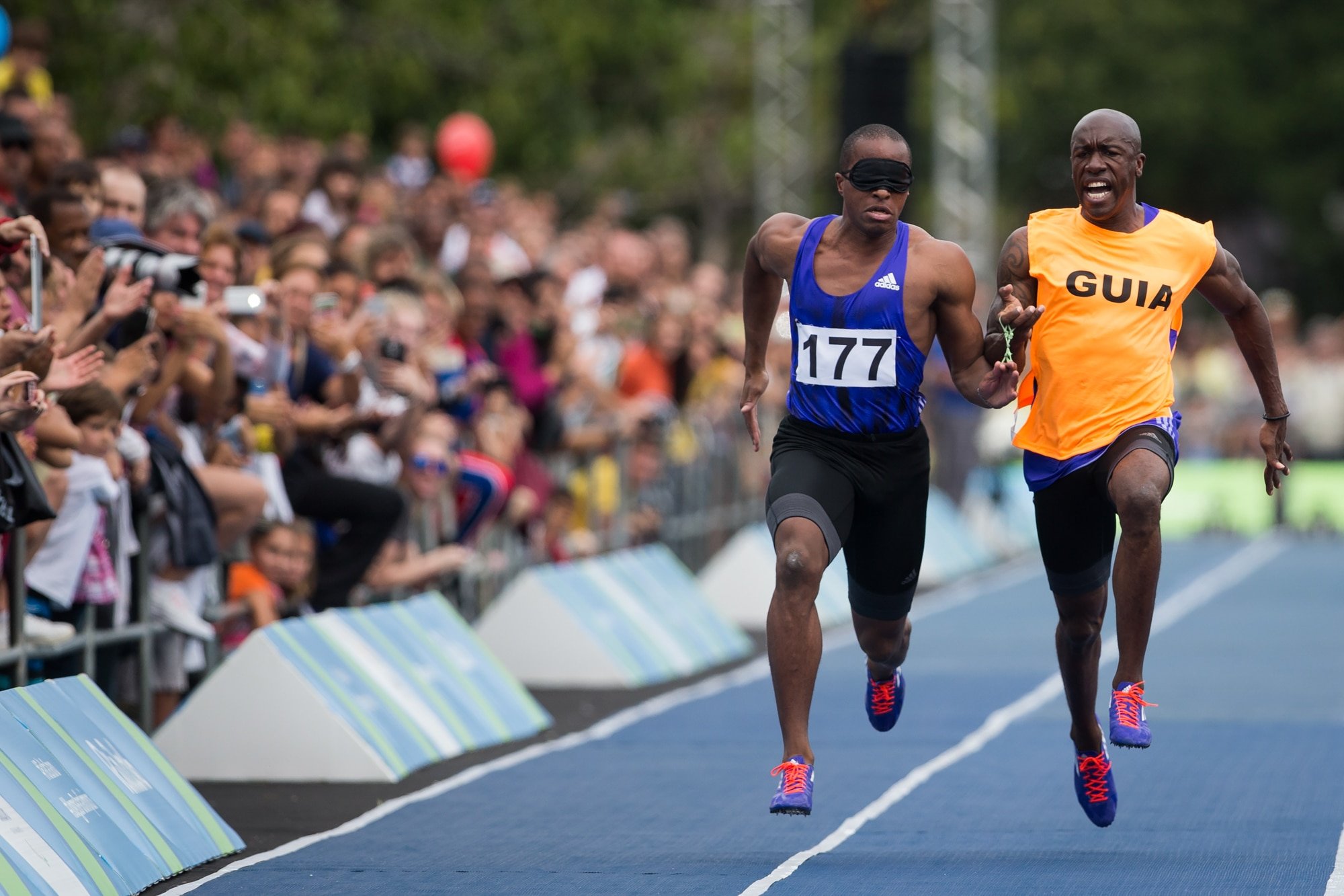 Two men running on track, one wearing blindfold (© AP Images)