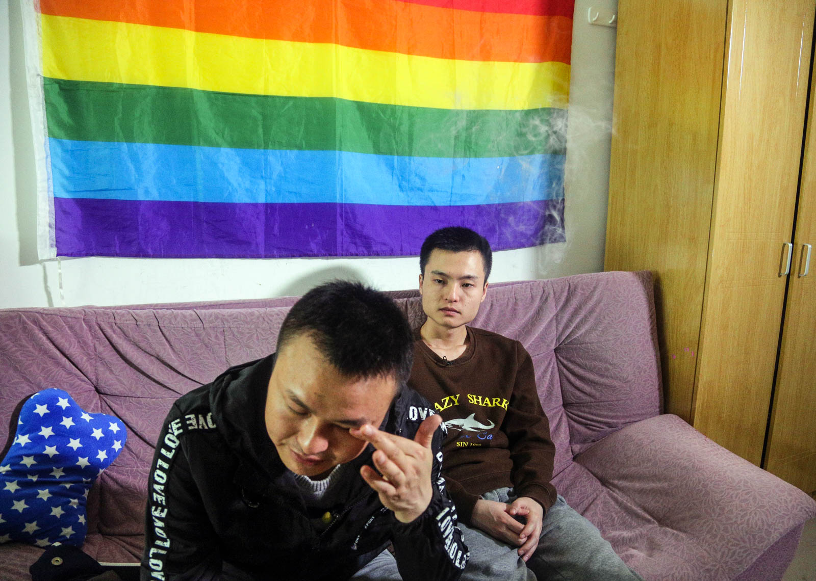In this photo taken Tuesday, April 12, 2016, Sun Wenlin, right, sits with his partner Hu Mingliang at home a day before going to court to argue in China's first gay marriage case in Changsha in central China's Hunan province. A judge on Wednesday, April 13, 2016 ruled against the gay couple in China's first same-sex marriage case that attracted several hundred cheering supporters to the courthouse and was seen as a landmark moment for the country's emerging LGBT rights movement. (AP Photo/Gerry Shih)