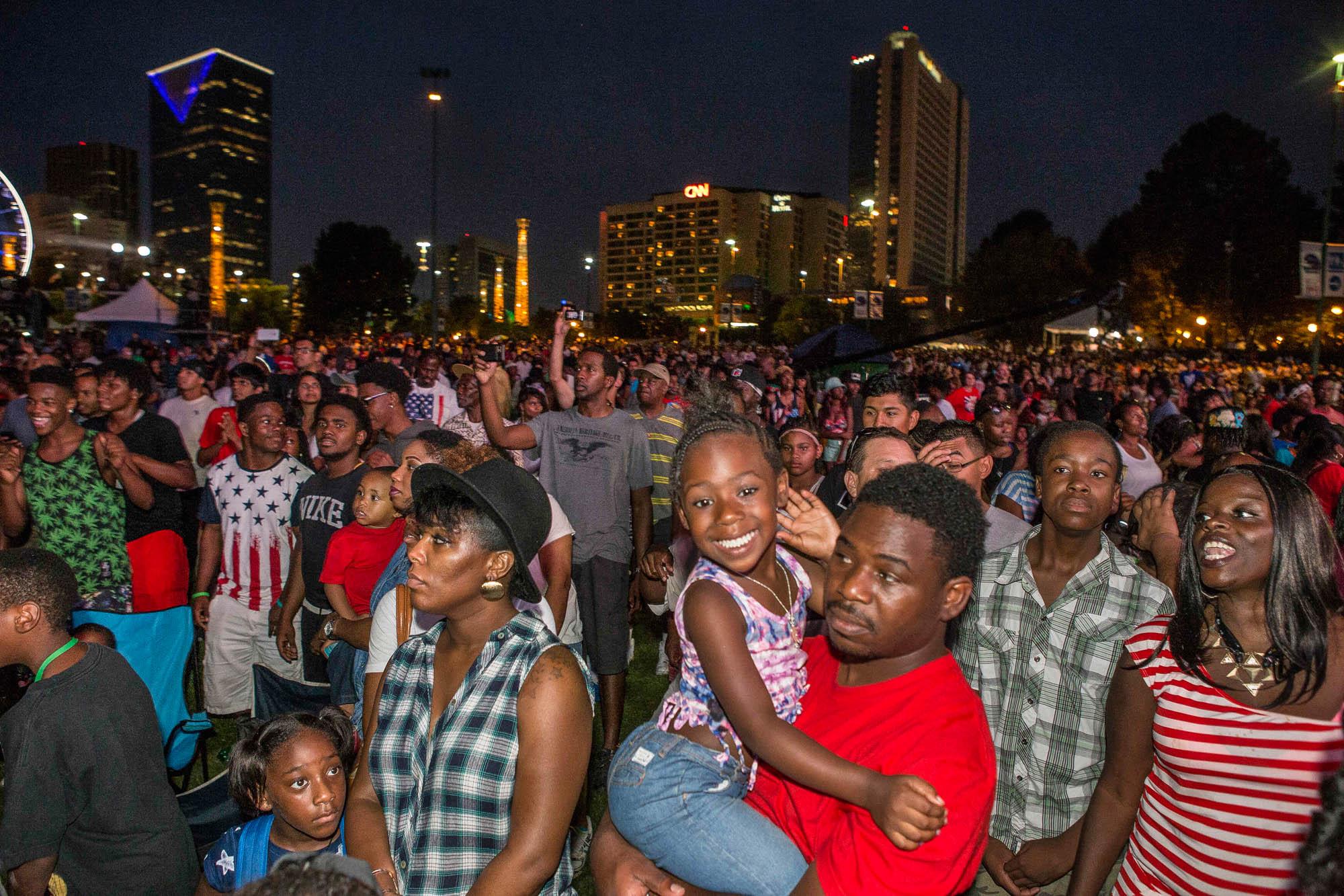 Men, women and children watching outdoor concert (© AP Images)