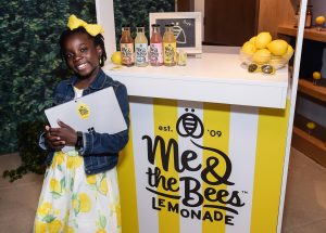 Girl holding laptop computer and leaning against lemonade stand (© AP Images)