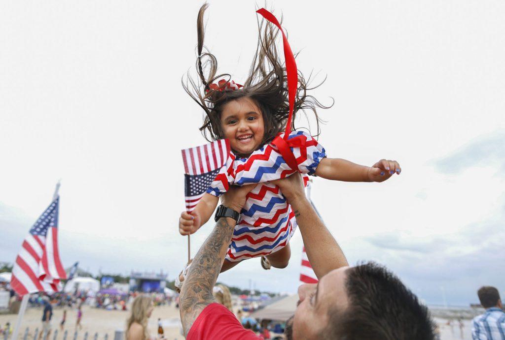 Homem ergue criança no ar (© Jonathan Bachman/Discovery Communications/AP Images)