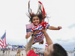 مردی دخترش را به سوی آسمان بلند کرده است. (عکس از آسوشیتد پرس)