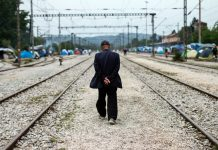 Man walking along railroad tracks (© AP Images)