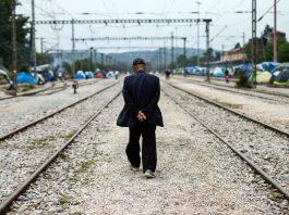 Man walking along railroad tracks (© AP Images)