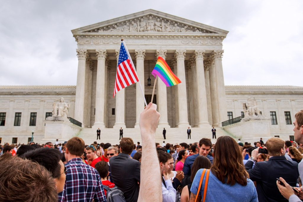 Crowd waving the American and LGBTI flags in front of large building (© AP Images)