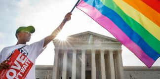 Man waving flag in front of U.S. Supreme Court (© AP Images)