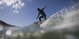 Surfer riding wave (© AP Images)