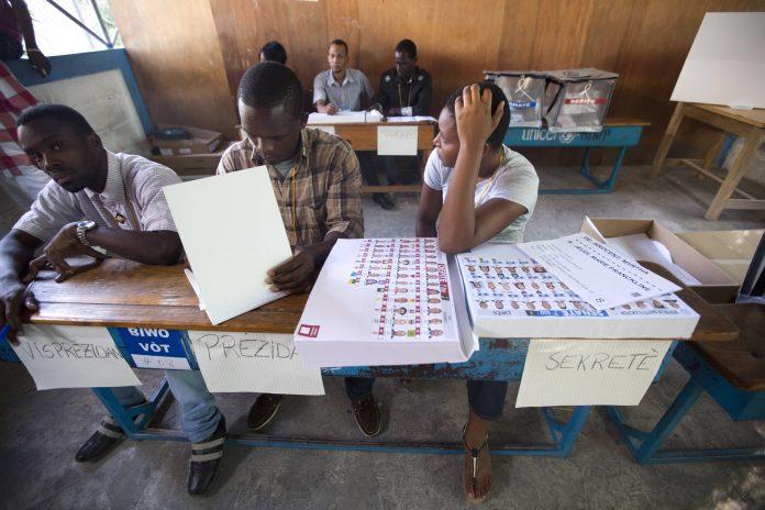 Trabajadores electorales sentados, esperando a los votantes (© AP Images)