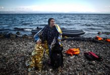Female refugee and her child wrapped in blankets walking on beach (© AP Images)