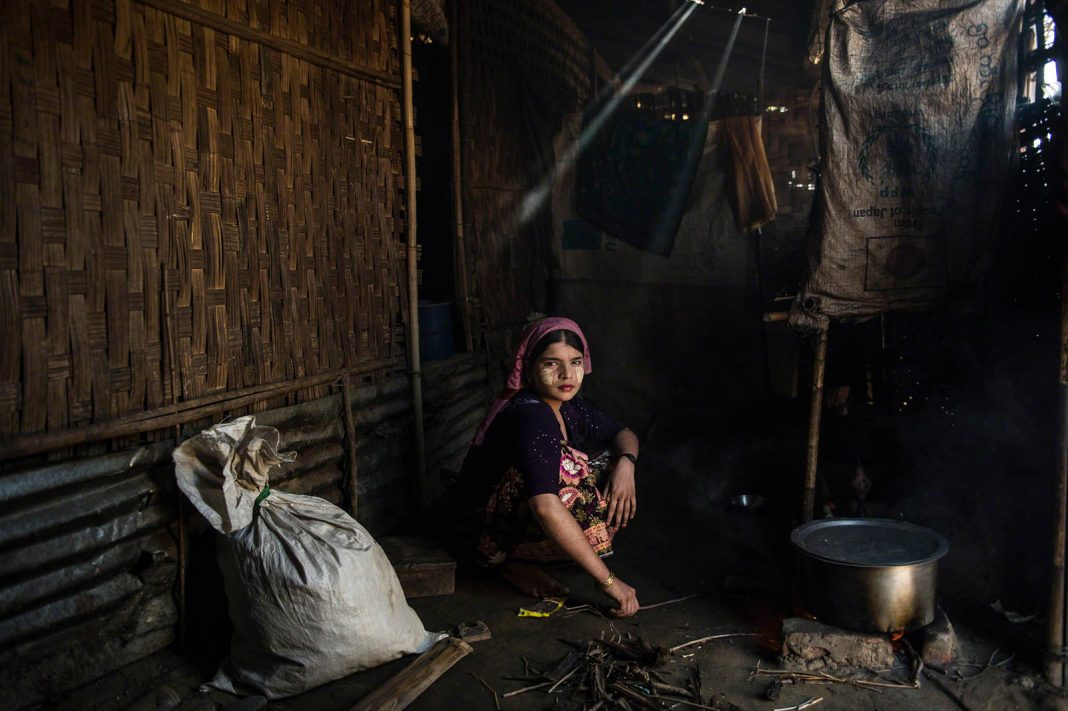 Uma mulher cozinha na casa de sua família no campo de refugiados Say Tha Mar Gyi, em Mianmar. Ela é casada, mas seu marido a deixou no ano passado para voltar para a família dele (© Lynsey Addario/Cortesia: Espaço Annenberg para Fotografia)