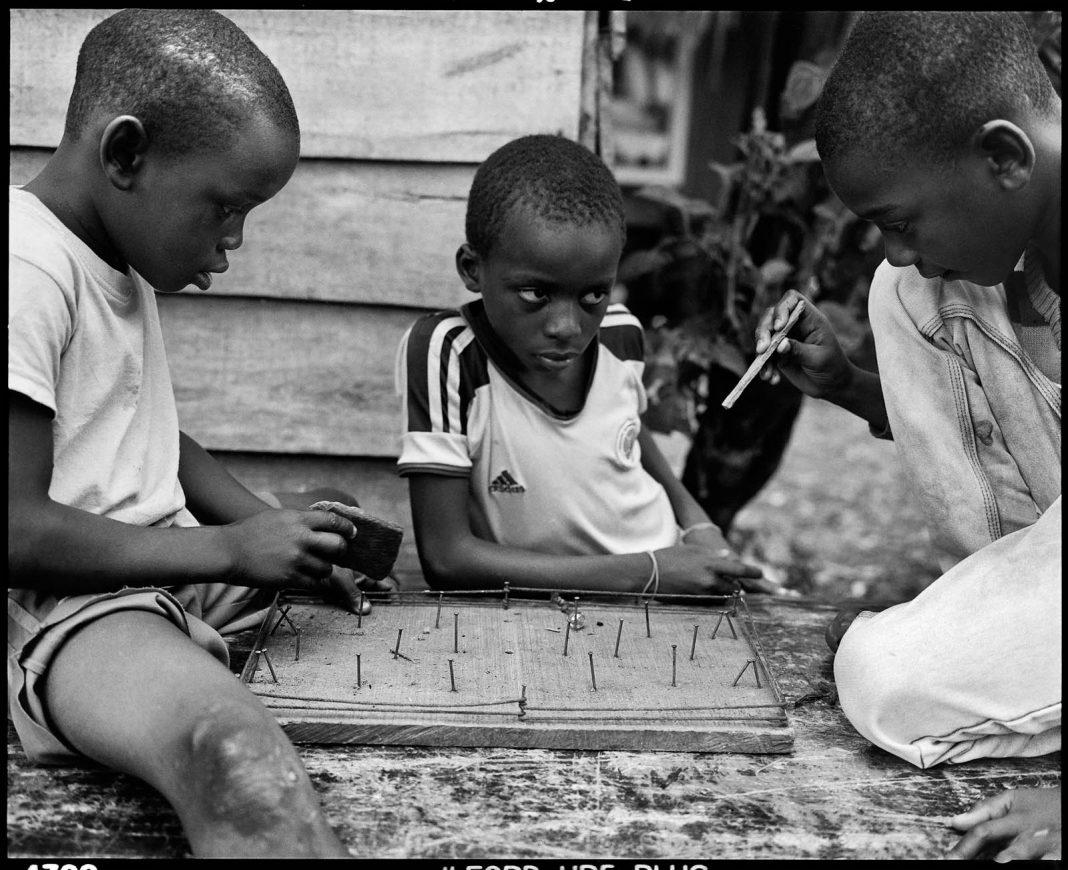 Três meninos brincando com um jogo (© Graciela Iturbide/Cortesia: Espaço Annenberg para Fotografia)