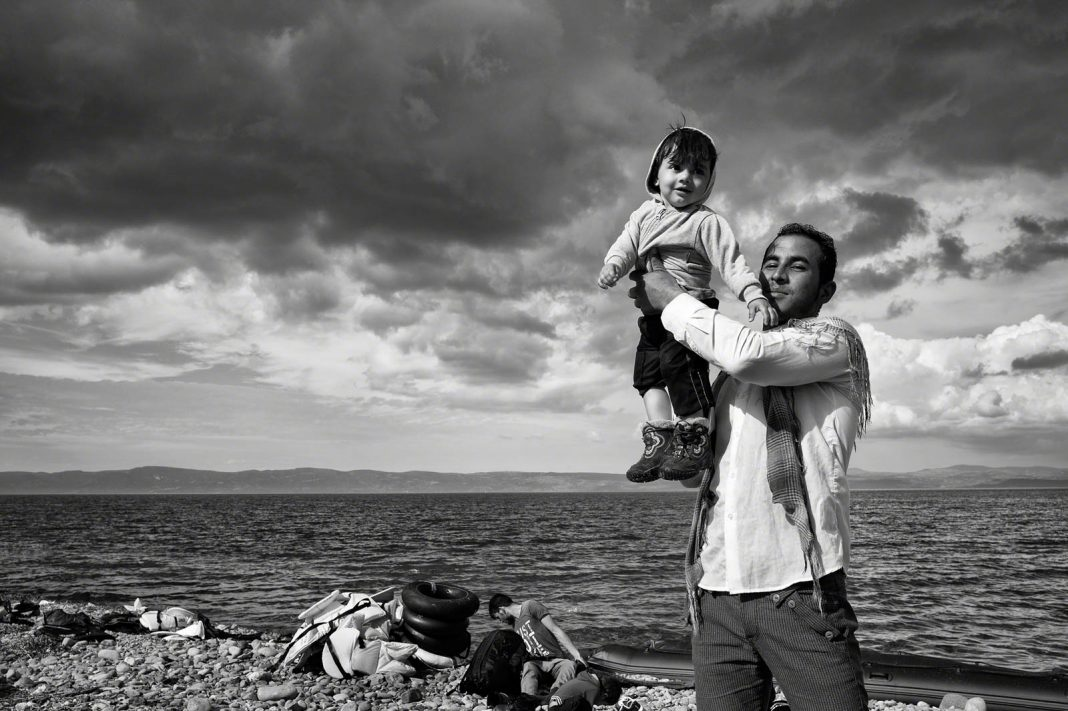 Man holding up child on rocky beach (© Tom Stoddart/Getty Images/Courtesy of Annenberg Space for Photography)