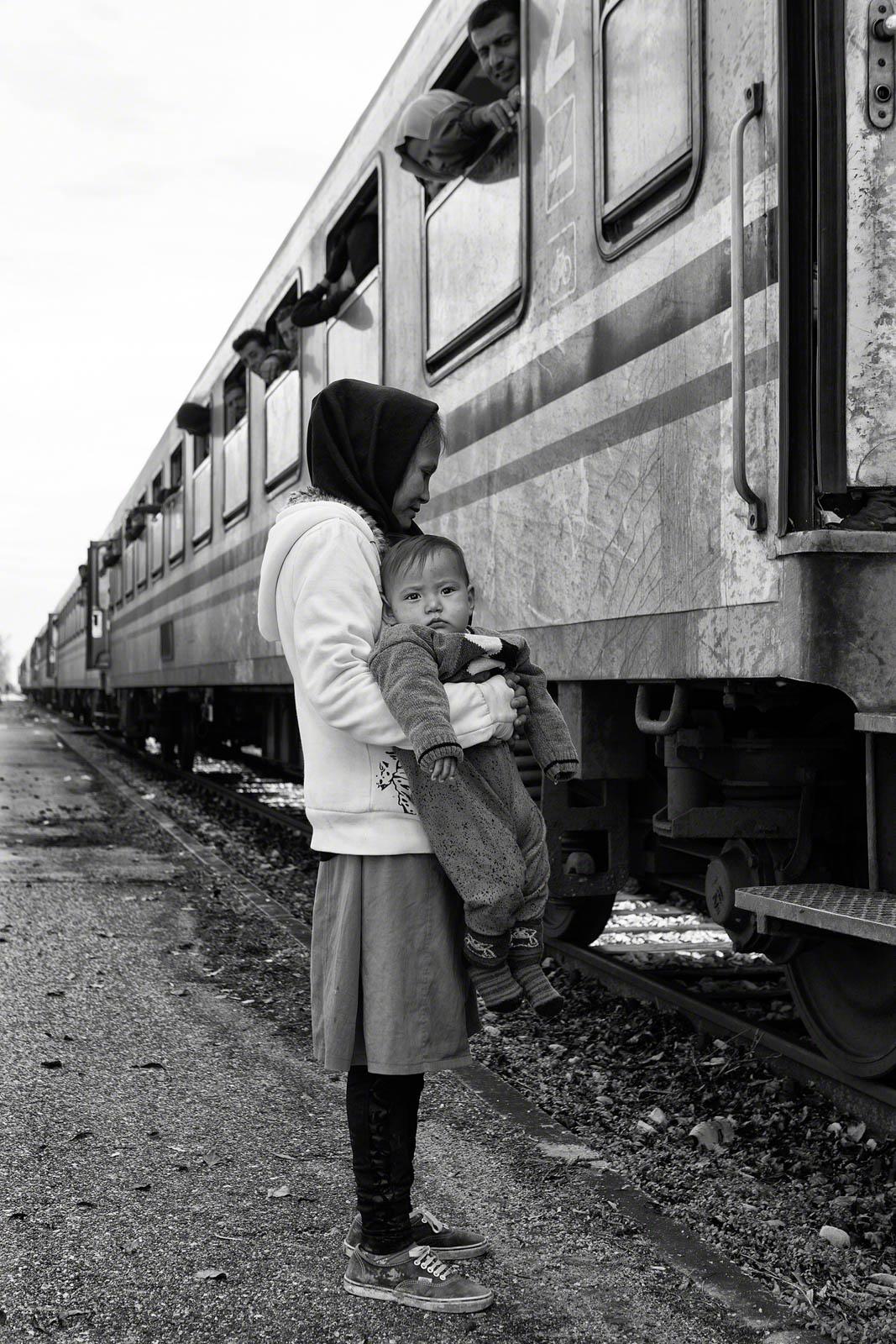 امرأة تحمل طفل وتقف بجانب القطار (© Tom Stoddart/Getty Images/Courtesy of Annenberg Space for Photography)