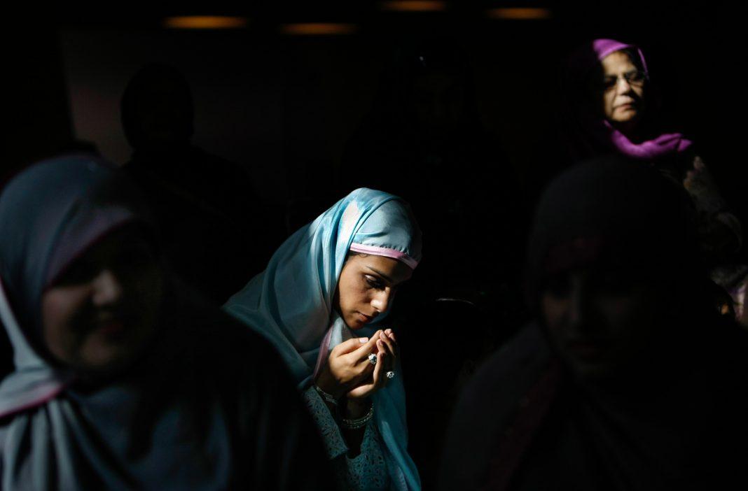 Women praying in shadows (© Getty Images/Allen J. Schaben)